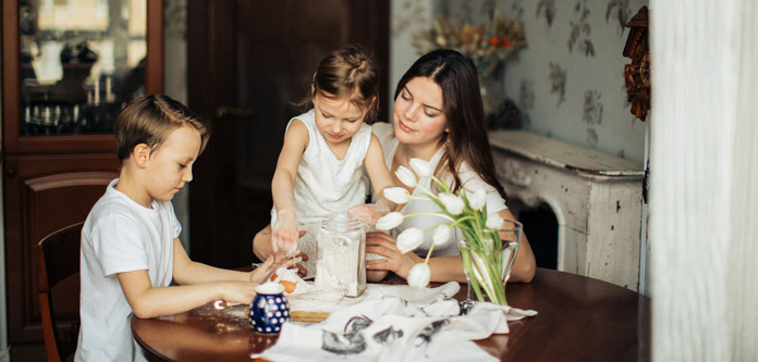 woman-sitting-near-the-table-with-her-children